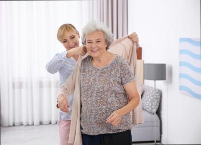 Caregiver helping senior women to put on cardigan at home