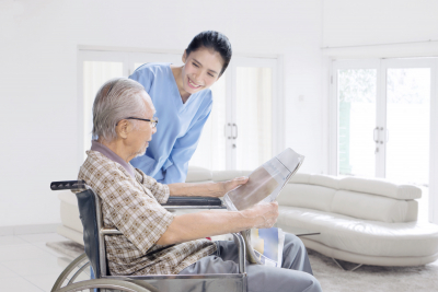 senior man reading newspaper with his caregiver